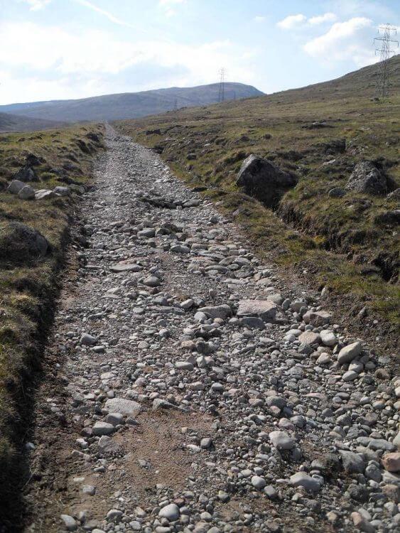 """General Wade's """"Strasse"""" ist mit dickem Schotter gepflastert und geht den ersten Kilometer schnurgerade berghoch. Viele Bäche queren den Weg in mit groben Blöcken gesicherten Rinnen"""