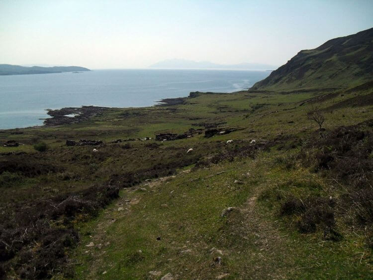 """Hier stehen zwischen Schafen die Ruinen des Ortes <a href=""""https://en.wikipedia.org/wiki/Boreraig"""" rel=""""noopener"""" target=""""_blank"""">Boreraig</a>, dessen Bewohner, wie viele andere im Zuge der sogenannten <a href=""""https://de.wikipedia.org/wiki/Highland_Clearances"""" rel=""""noopener"""" target=""""_blank"""">Highland Clearances</a> in der Mitte des 19.Jh. gewaltsam vom Adel vertrieben wurden, um Platz für Weideland zu schaffen.<br>Am Horizont ist die Insel Rum"""