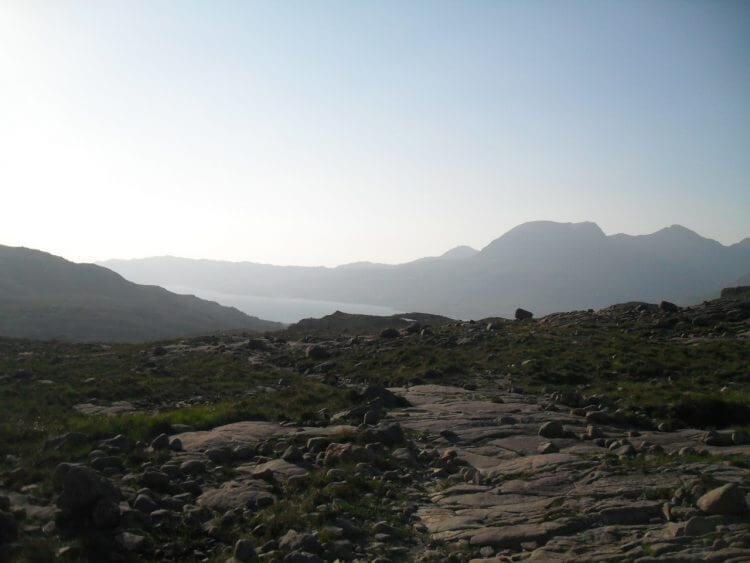 Auf der Passhöhe angekommen geht es auf breitem Weg mit extrem grobem und lockerem Schotter wieder abwärts