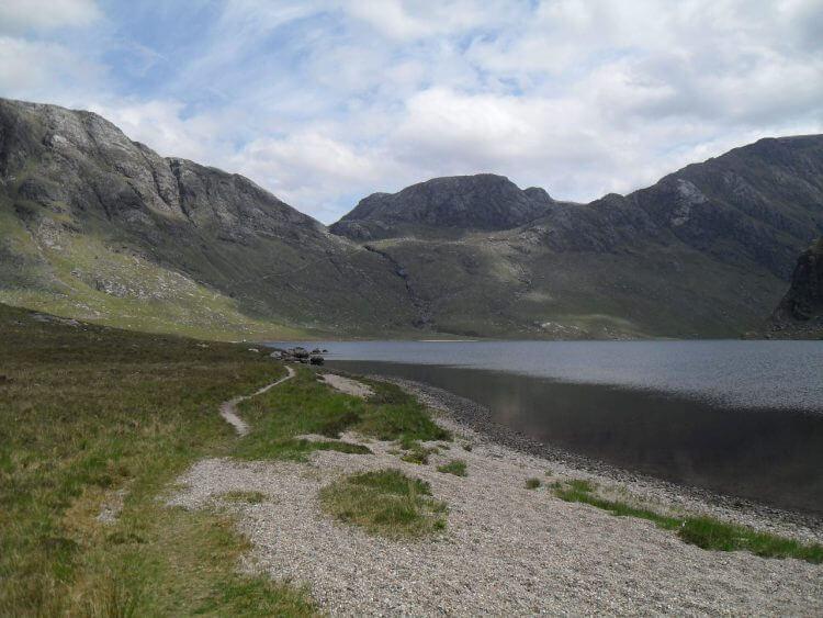 Direkt danach zieht sich der Pfad über 2 km die Flanke des Beinn a'Chàisgain Mòr hoch und führt dann in das Hängetal des Allt Bruthach an Easain. Dessen Abfluß ist die Rinne in der Bildmitte und links davon kann man den Pfad erkennen.