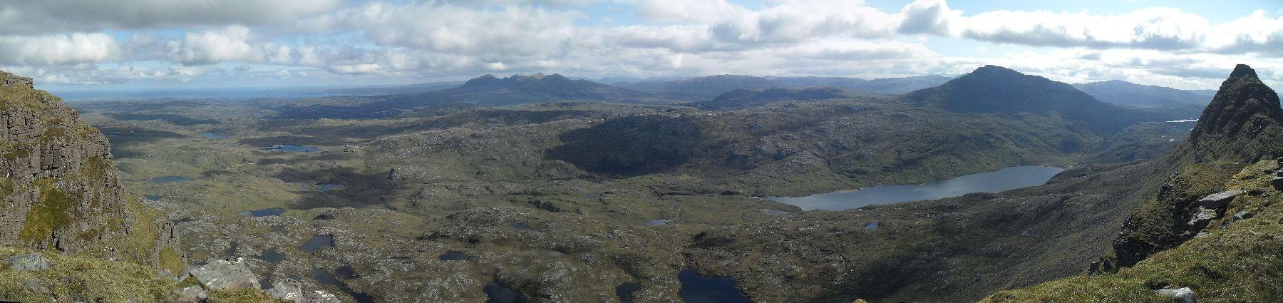 Blick nach Norden. Am Horizont das Quinag-Massiv,  rechts Canisp (847m) und Loch na Gainimh. In der Mitte der linken Bildhälfte, der schmale weiße Strich, ist die Suileag Bothy