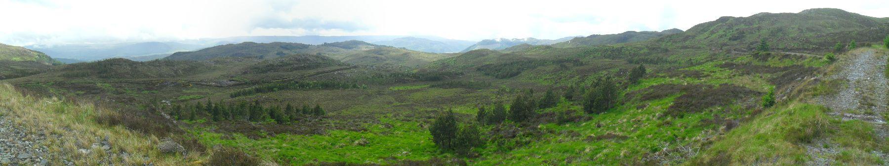 Der Weg macht am Talende eine 180-Grad-Wende und verläuft auf breitem Schotterweg auf gleichbleibender Höhe den Hang entlang. Horizontal in der Mitte der linken Bildhälfte sieht man den zurückliegenden Weg, rechts den vor mir liegenden, in der Bildmitte im Sonnenschein die GGW-High-Route und dahinter einen schmalen Streifen von Loch Ness. Der Abstecher hat sich jetzt schon gelohnt