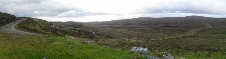 """Nach 8km ist die <a href=""""https://www.mappit.net/layers/mountain-bothies-in-scotland/#bothy=492"""" rel=""""noopener"""" target=""""_blank"""">Hydro-Bothy</a> erreicht, ein ehemaliges Zementlager für den Bau der Wasser-Pipeline. Foto: Blick von der Bothy auf den Track. In der rechten Bildhälfte sieht man horizontal einen Teil der Pipeline, an der der Weg entlang läuft. Dieser macht dann einen Bogen zur Bothy hin und steigt dann in nahezu pfützenfreies Gelände an"""