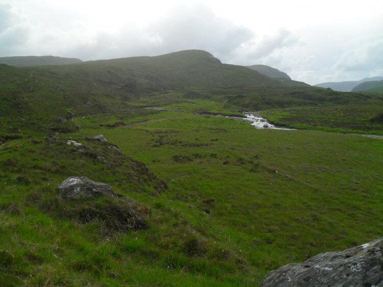 und plötzlich öffnet sich das Tal zu einer breiten Aue, dahinter der Hügel ist der Creag Dubh. Da muß ich hoch. Der Weg ist im Gegenlicht gerade so erkennbar. Aber es ist schon 20:30 Uhr und so werde ich mein Lager aufschlagen.  Hier oben, wo es etwas windiger ist, finde ich keinen Platz für das Zelt.
