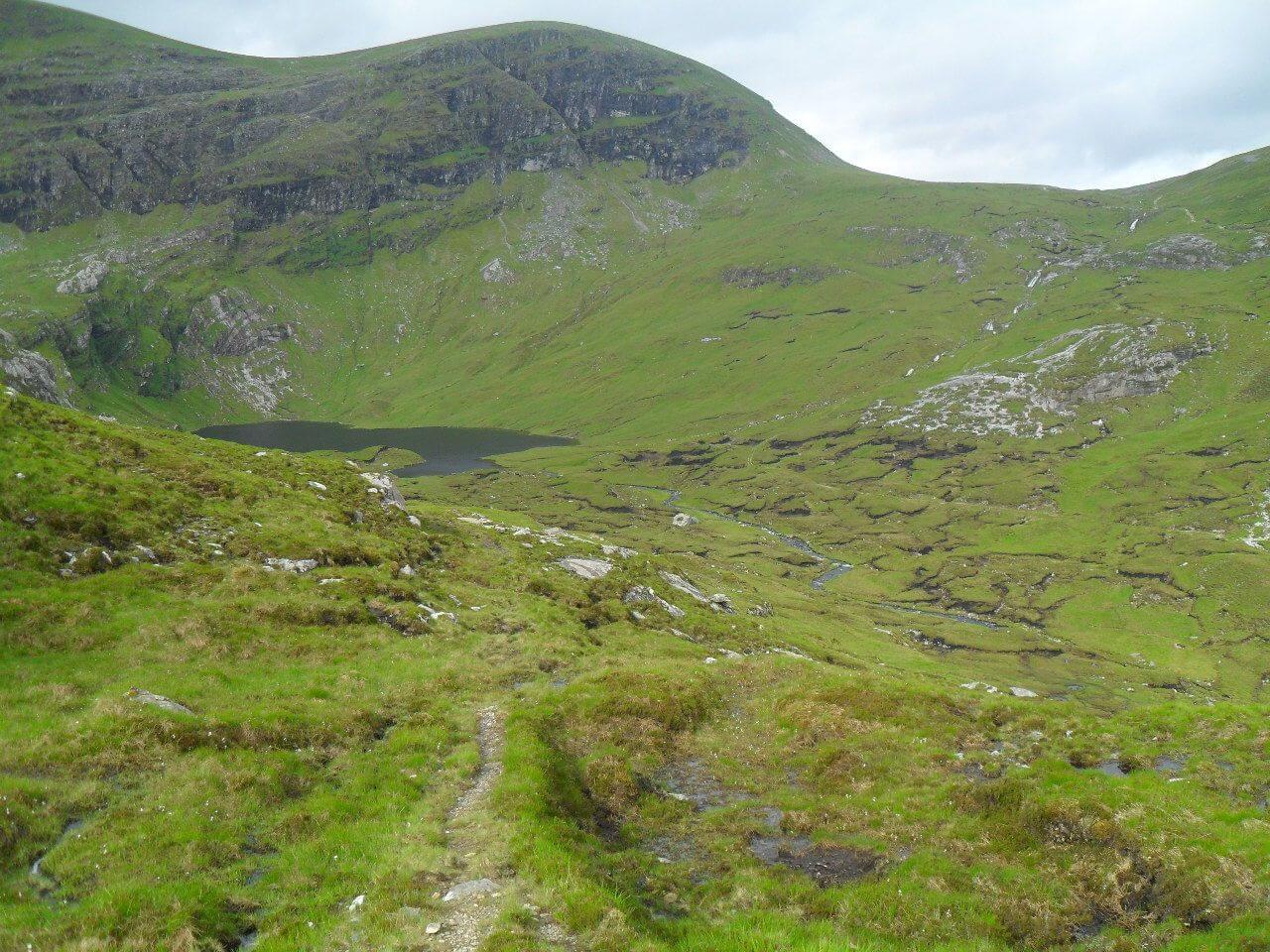 """Der Pfad ist jetzt überwiegend gut fahrbar. Schon bald geht es steil hinab zum Kar des <em>An Dubh Loch</em>, ein weiteres """"schwarzes Loch"""". Rechts oben sieht man den Pfad zum <em>Bealach Horn</em>"""