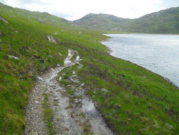 """Ich fahre an der Suileag-Bothy vorbei und an der Abzweigung zum Suilven-Aufstieg. Ab jetzt bin ich wieder auf unbekanntem Terrain. Entlang <em>Loch na Gainimh</em> wird der Weg schmaler und als er sogar für ein Argocat unfahrbar wird, steht dort ein ebensolches und der Fahrer daneben, mit dem Fernglas nach Hirschen Ausschau haltend. <em>""""That's not really a bike route""""</em>, sage ich, und er <em>""""Indeed, it's probably not the best track in the world, isn't it""""</em>. So sind sie, die Briten"""