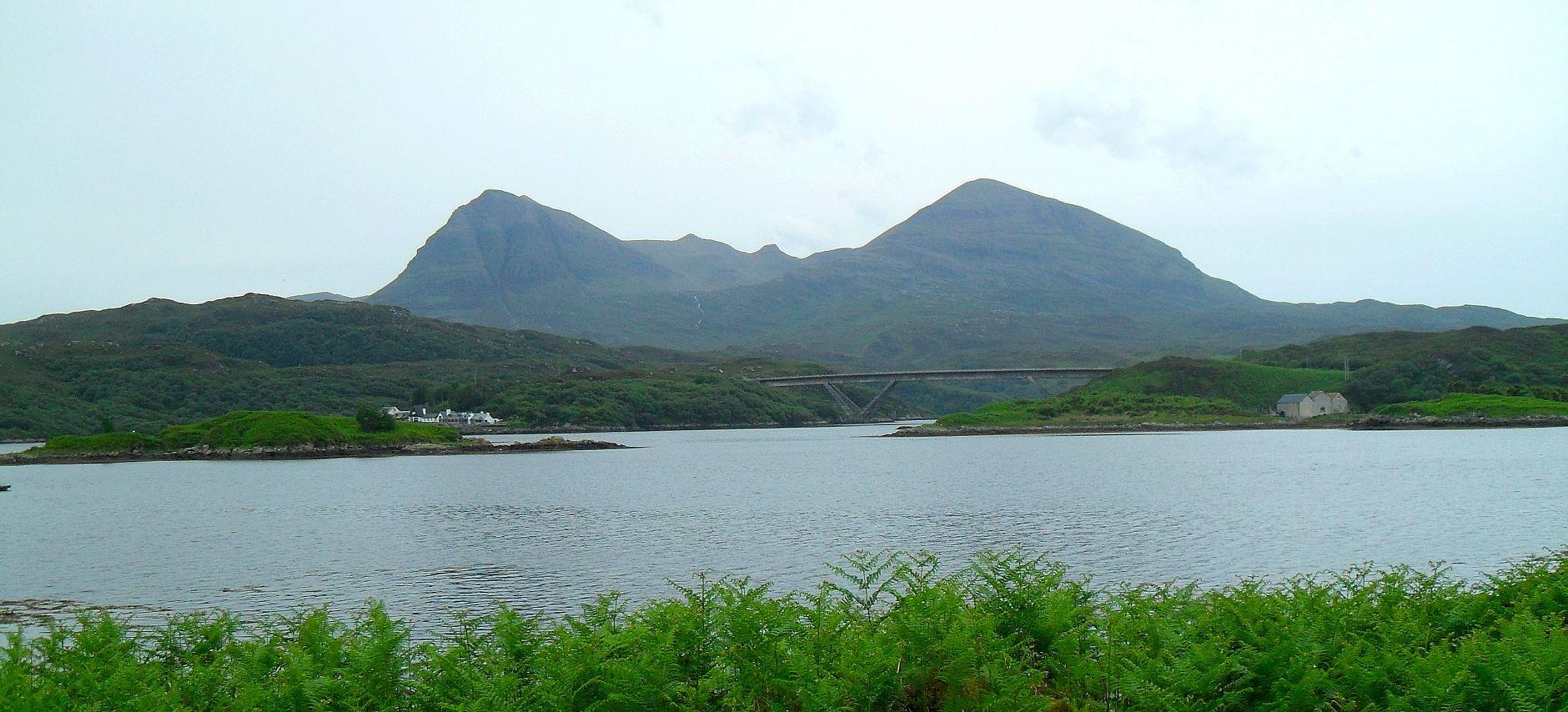 Quinag-Massiv, davor die Kylesku-Bridge, die die Meerenge zwischen <em>Loch Glendhu</em> und <em>Loch a' Chàirn Bàin</em> überspannt. Links davon Kylesku, da will ich hin. Der Weg dorthin geht erst weiter am Loch vorbei, dann auf der A894 über die Brücke